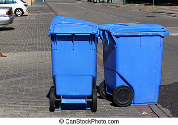 Blue garbage cans on the sidewalk