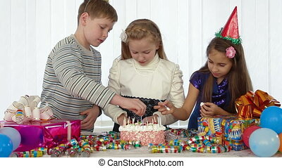 Three kids during birthday party - children decorate a...