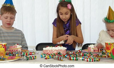 Little girl cuts the Birthday cake giving portions of their...
