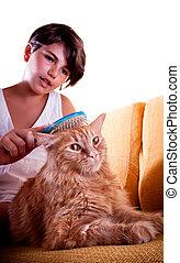 Girl grooming her cat