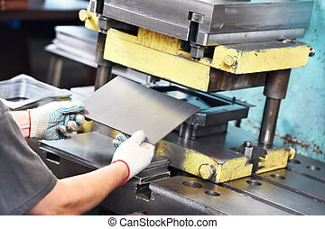worker operating metal sheet press machine - worker at...