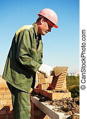 construction mason worker bricklayer making a brickwork with...