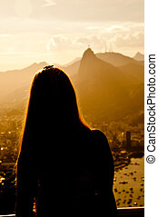 Woman viewing Christ the Redeemer from the top of the Sugar Loaf in Rio de Janeiro, Brazil