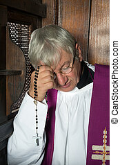 Confession box and priest - Vicar or priest sitting in a...