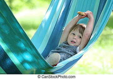 little girl on a hammock on nature