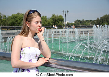 Young woman near fountain in a park - Romantic young woman...