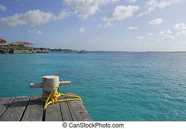 Mooring bollard on a wooden dock in the caribbean. - A steel...