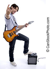young rock star holding guitar with one leg on speaker...