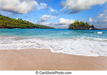 View from a sandy beach on rocks at ocean. Indonesia, Bali