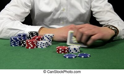 Poker player showing his hand - Poker player with a stack of...