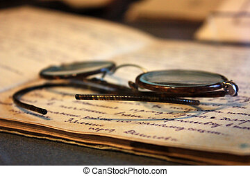 old glasses lying on the handwritten notebooks