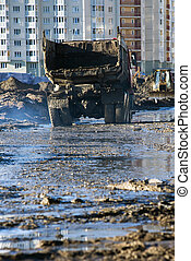 Muddy dump truck - Dirty and dented old dumptruck at a muddy...
