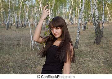 beauty girl stands with birch twigs
