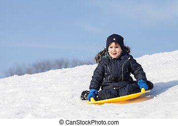 Sledding at winter time - Boy on sleigh. Sledding at winter...