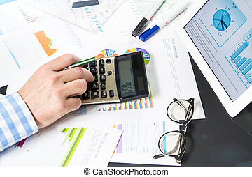 Calculating with business documents - Businessman uses his...