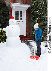 Person shovelling snow - Adult shovels snow off path outside...