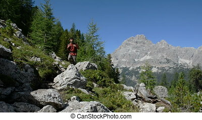 Adventurous mountain trekking - Young man hiking sorrounded...