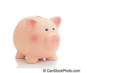 Saving money - Hand putting coins in a piggy bank....