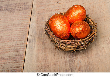Small bird's nest with orange foil eggs