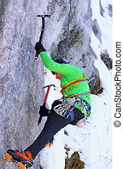 climbing an ice wall - climber in action with two axes on a...