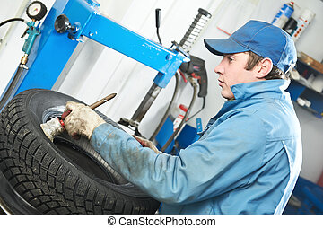 repairman mechanic lubricating car tyre - serviceman...