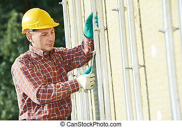 builder at aerated facade tile installation - worker builder...