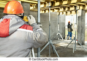Surveying works at construction site - Surveyor worker and...