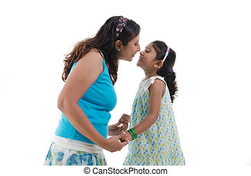 happy looking indian mother and daughter kissing
