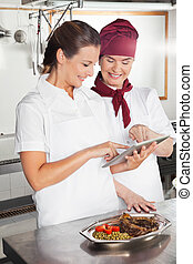 Female Chefs Using Digital Tablet In Kitchen - Happy female...