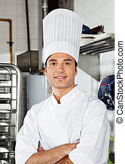 Young Chef With Arms Crossed In Kitchen - Portrait of...