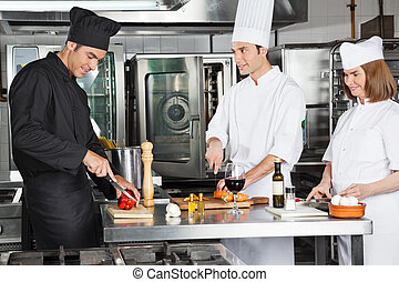 Chefs Working In Commercial Kitchen - Three professional...
