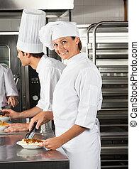Female Chef Working In Restaurant Kitchen