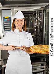 Mature Female Chef Presenting Pizza