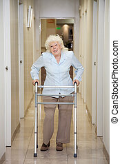 Elderly Woman With Walker In Hospital Corridor - Full length...