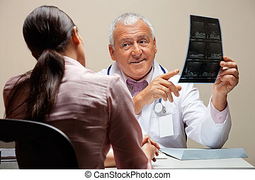 Radiologist Showing X-ray To Patient - Senior male...