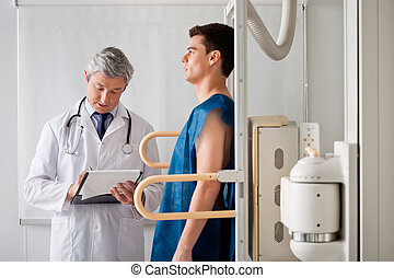 Male Patient Undergoing X-ray Test - Mature radiologist...