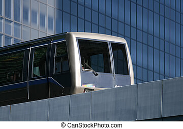 monorail - A modern transit train runs past a glass office...