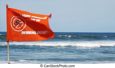 swimming prohibited - red flag on the sea beach