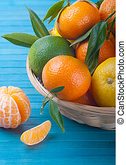 Tangerines and lemon  in a basket on a blue table
