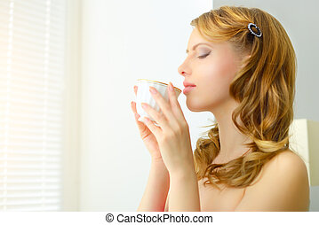 Morning Coffee - young attractive girl holding a cup of...