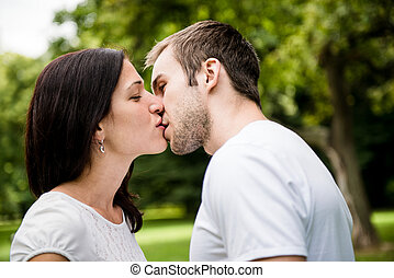 Young kissing couple in love - Young happy couple kissing -...