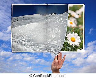 Book of seasons - Hand through the book of seasons on cloudy...
