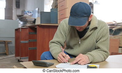 Furniture maker at work - Furniture maker calculating layout...