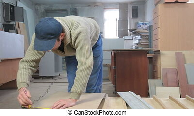 Furniture maker cutting wood panel