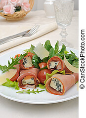 Appetizer of rolls with ham and blue cheese in a salad of lettuce with slices of Parmesan cheese