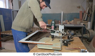 manufacturing furniture - carpenter drills a hole...