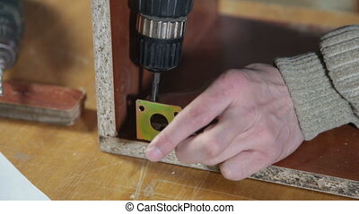 Furniture maker at work in workshop, using screwdriver