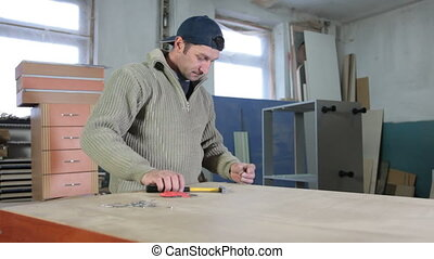 Furniture maker at work in workshop, driving nails with a...