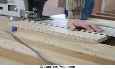 Furniture maker at work in workshop, cutting wood panel