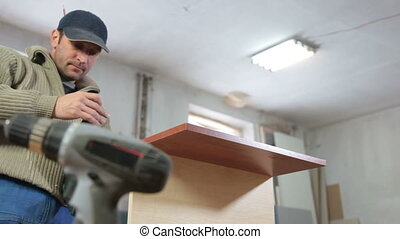 manufacturing furniture - Furniture maker at work in...